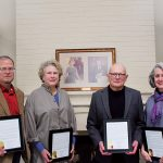 David Turk, Ann Ross, John Herron, and Becky Sykes pose with Resolutions of Appreciation presented to them by the Board of Trustees for their work on the house renovation. The photos of Mae and Robert Wood are behind them on the mantel.